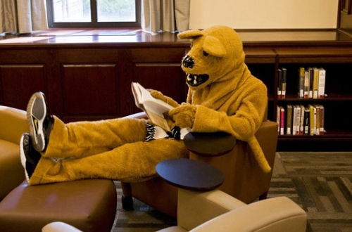 Nittany Lion enjoying a book in the Leisure Reading Room