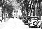 1930s Pattee Library in snow with old cars parked along Pattee Mall and tall elm trees